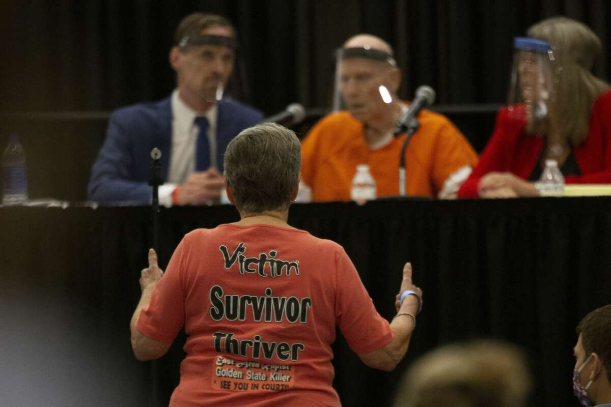 Jane Carson-Sandler, a 1976 rape victim of Golden State Killer Joseph James DeAngelo, stands and gives a double thumbs-up to agree with a prosecutor's statement about part of DeAngelo's anatomy, during a court hearing in Sacramento, Calif., Monday, June 29, 2020. DeAngelo, 74, pleaded guilty to 13 counts of murder and multiple other charges 40 years after a sadistic series of assaults and slayings in California. Due to the large numbers of people attending, the hearing was held at a ballroom at Sacramento State University to allow for social distancing. (AP Photo/Rich Pedroncelli)