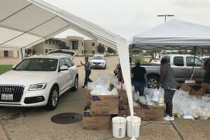 State Rep. Gary Gates and his team hand out kits of personal protective equipment, hand sanitizer and toilet paper to area residents at Tompkins High School in Katy on Friday, June 26.