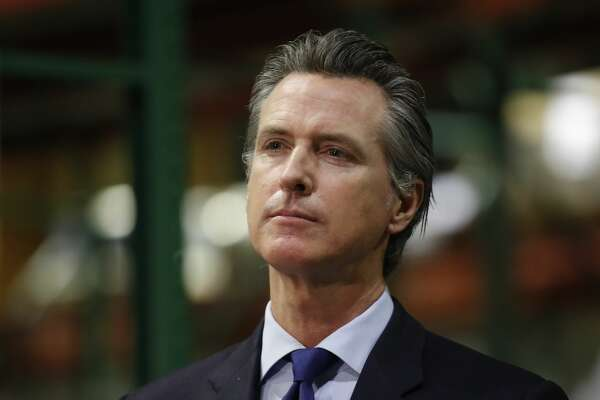 Gov. Gavin Newsom listens to a reporter's question during a news conference in Rancho Cordova, Calif., Friday, June 26, 2020. Newsom has pardoned 13 former prisoners, including three whose immigration status may benefit. He also commuted the sentences of 21 current inmates on Friday, including several who killed their victims and had been serving life-without-parole sentences.