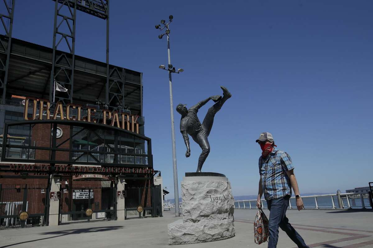 The statue of Hall of Fame pitcher Juan Marichal is shown behind a man wearing a mask outside of Oracle Park, the San Francisco Giants' baseball ballpark, during the coronavirus outbreak in San Francisco, Thursday, June 25, 2020.