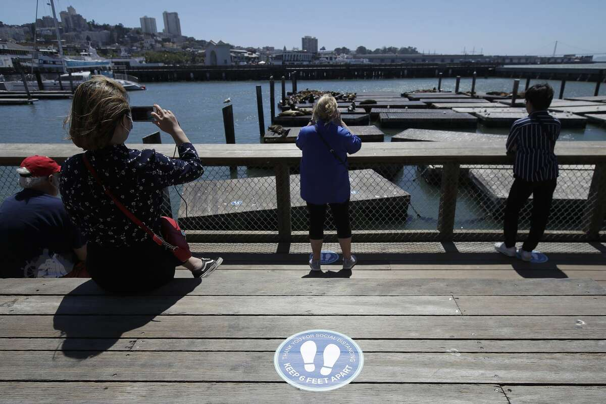 In this June 18, 2020, file photo, a sign advising visitors to maintain social distance is shown as people watch the sea lions at Pier 39, where some stores, restaurants and attractions have reopened, during the coronavirus outbreak in San Francisco. Health officials in Santa Clara County, California, one of the most aggressive in the nation in shutting down because of the coronavirus are warning of