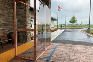 "This handout photo provided Carlson Management and taken in the spring of 2020 shows a plexiglass cubicle, dubbed the ""Sneezeguard 3000,"" at the Rockville Terrace assisted living home in Fairfield, California. A staff member built this and other cubicles for the company's three assisted living homes in California so that family members could visit safely with family members while on their phones during the coronavirus pandemic. They started using the cubicles in April and report that they've had very little coronavirus in their facilities due to these and other safety measures."
