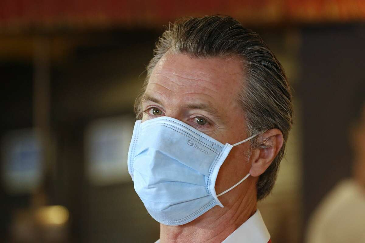 In this June 19, 2020, file photo, California Gov. Gavin Newsom, wears a face mask as he answers a reporter's question during his visit to the Queen Sheba Ethiopian Cuisine restaurant in Sacramento, Calif. Newsom implored people Monday, June 22, 2020, to wear face coverings to protect against the coronavirus and allow businesses to safely open after several days in which the state saw its highest virus hospitalizations and number of infections to date.