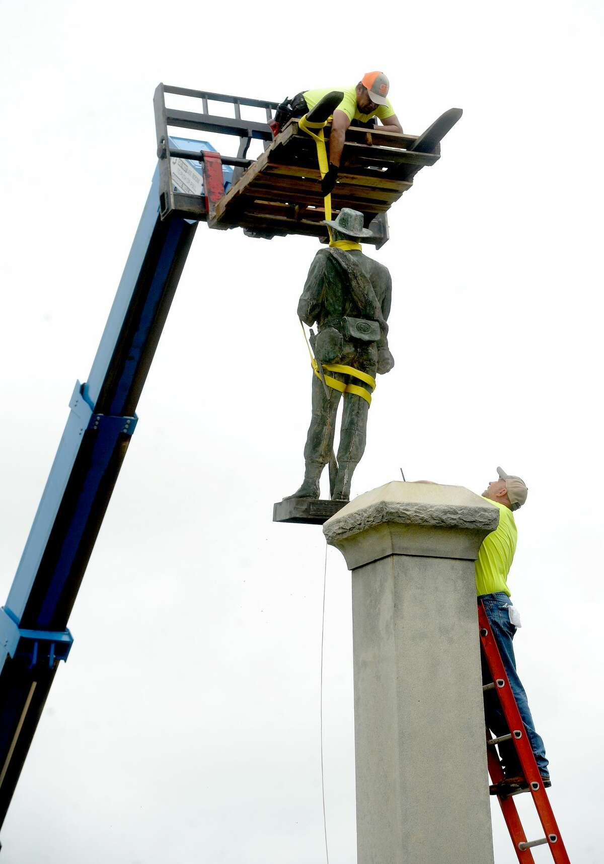 Workers with the City of Beaumont and Marsh Waterproofing, Inc., which does restoration work, dismantle and remove the Confederate monument in Wiess Park Monday. The city moved swiftly to remove the monument following last Tuesday's city council approval. Photo taken Monday, June 29, 2020 Kim Brent/The Enterprise