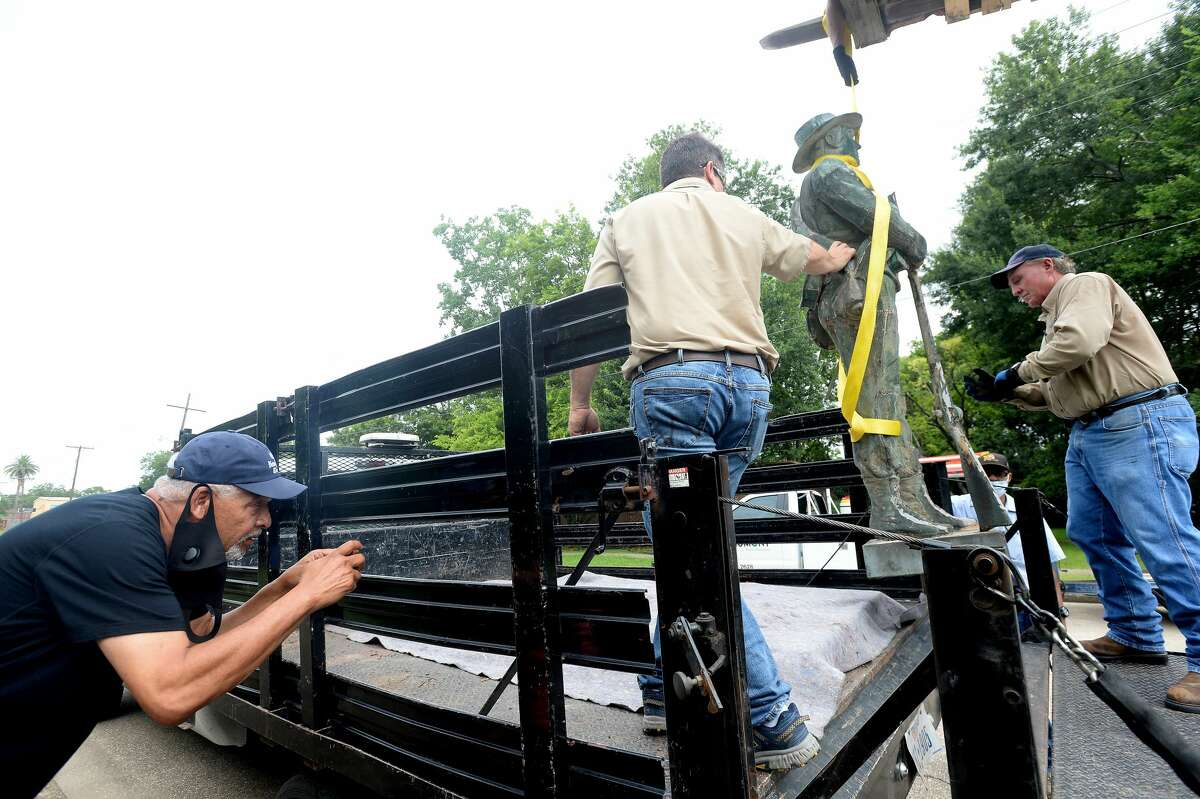 Oliver Sprott leans in to get a photograph as the Confederate soldier is carried to a flatbed to be transported to storage as workers with the City of Beaumont and Marsh Waterproofing, Inc., which does restoration work, dismantle and remove the Confederate monument in Wiess Park Monday. The city moved swiftly to remove the monument following last Tuesday's city council approval. Photo taken Monday, June 29, 2020 Kim Brent/The Enterprise