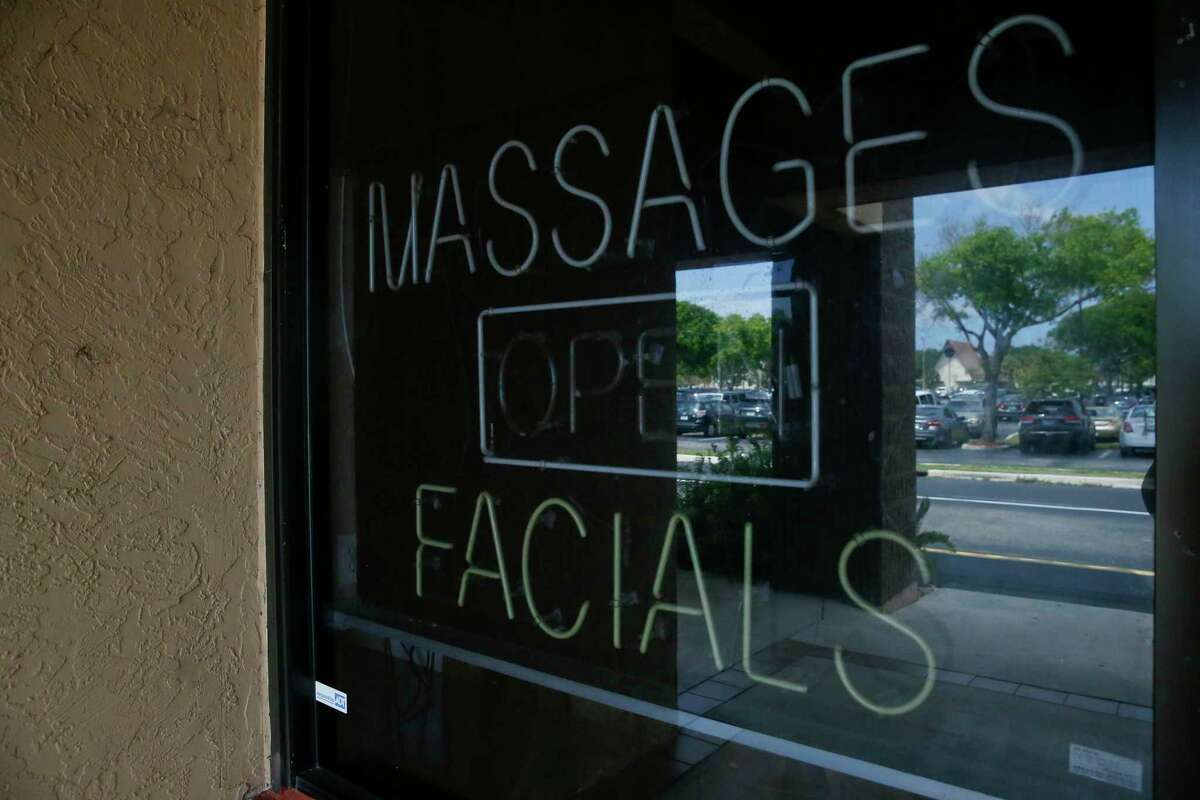 FILE - This March 26, 2019 file photo, shows a sign in the window of the front entrance of the Orchids of Asia Day Spa in Jupiter, Fla. Florida prosecutors will try to save their prostitution solicitation case against New England Patriots owner Robert Kraft when they argue before an appellate court Tuesday, June 30, 2020, that his rights weren't violated when police secretly video recorded him allegedly paying for sex at Orchids of Asia. (AP Photo/Brynn Anderson, File)