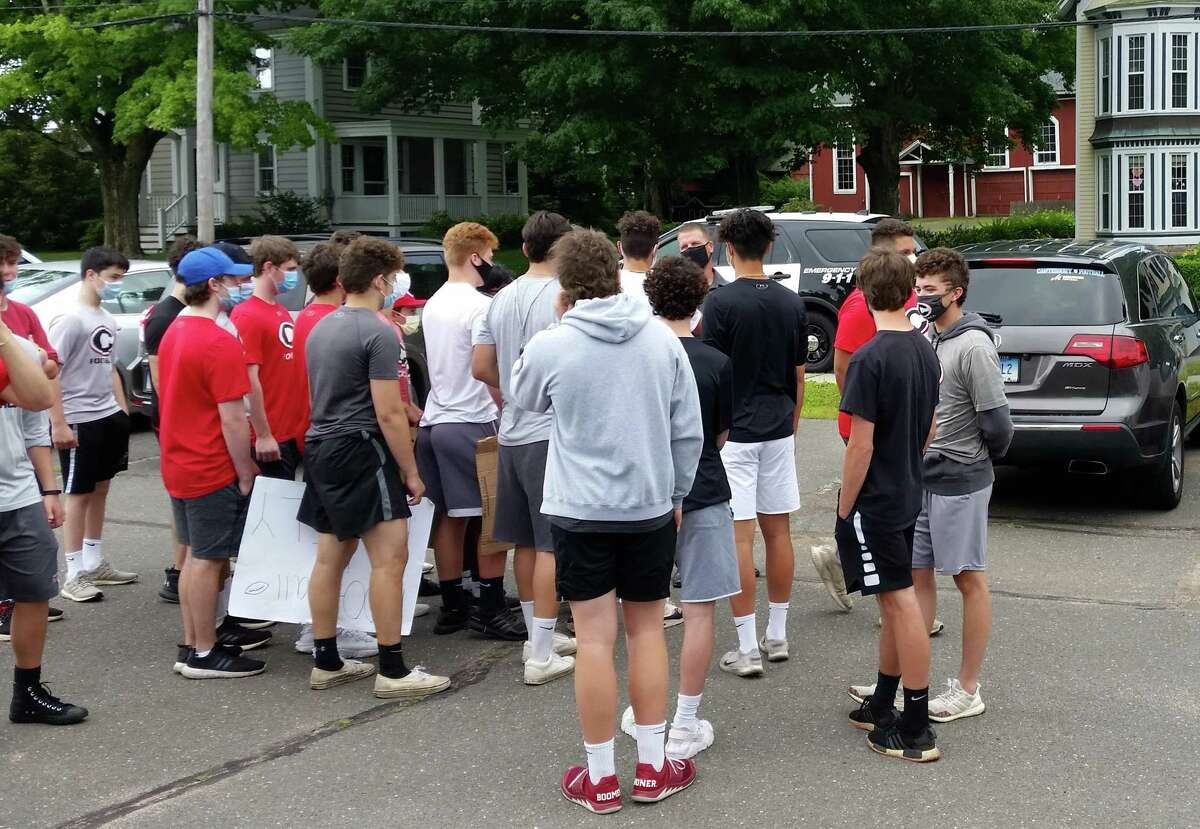 Cheshire football coach Don Drust (back, with black face mask) greets a crowd of students who came to the parking lot of Humiston School to support him. Drust met with the town's school administration early Monday morning, June 29, 2020.