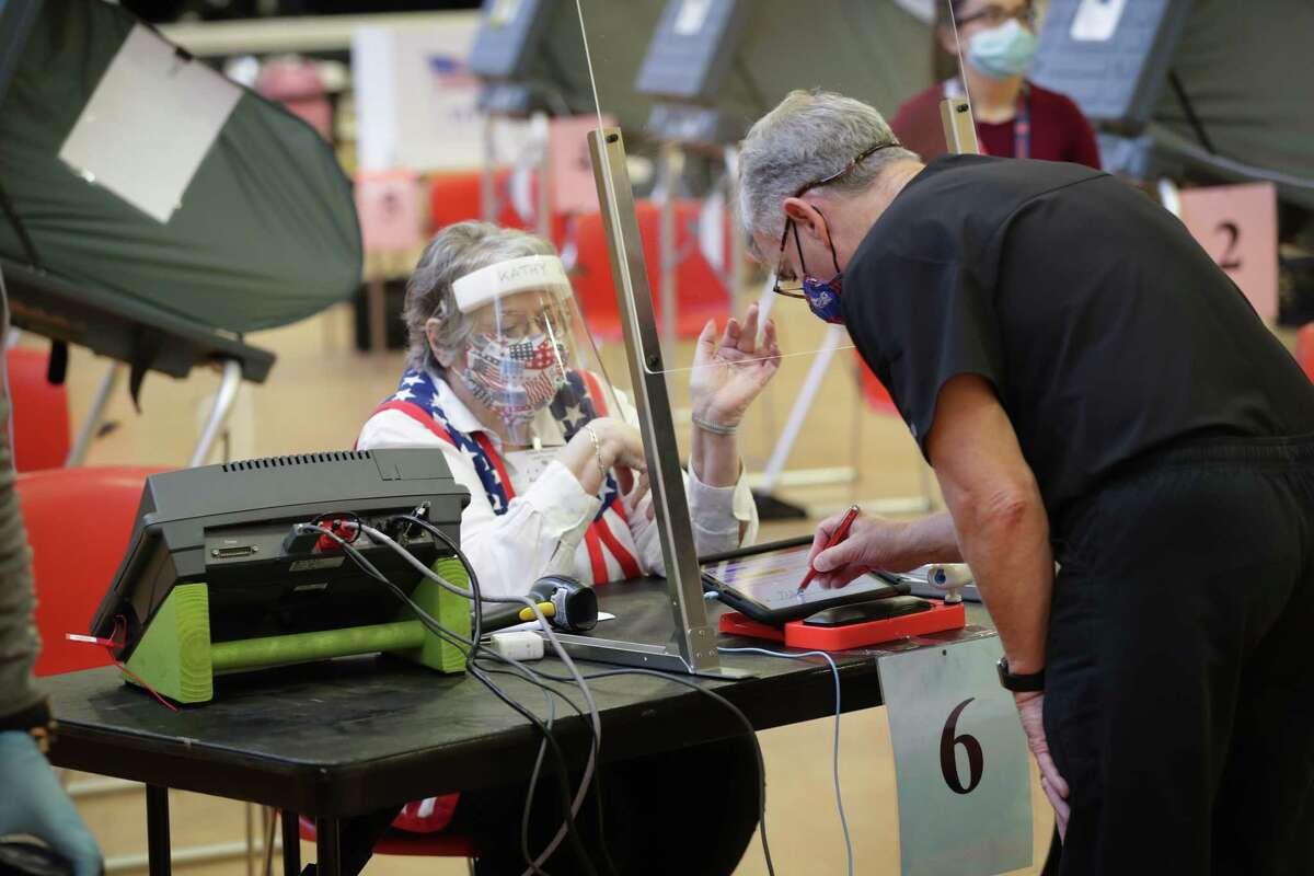 Kathy Kellen sits behind and wears a plastic shield and face covering as she helps an early voter at in the Metropolitan Multi-Services Center, 1475 W Gray St., Monday, June 29, 2020, in Houston.