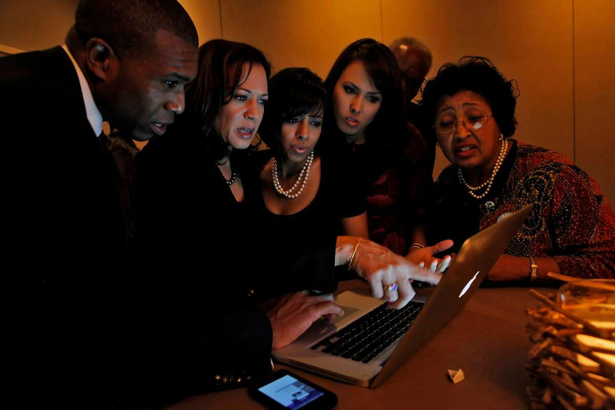 Tony West, left and Kamala Harris look up the poll results with family Maya Harris, Meena Harris and parents Frank and Peggy Harris at the Hotel Vitale, Tuesday Nov. 2, 2010, in San Francisco, Calif.