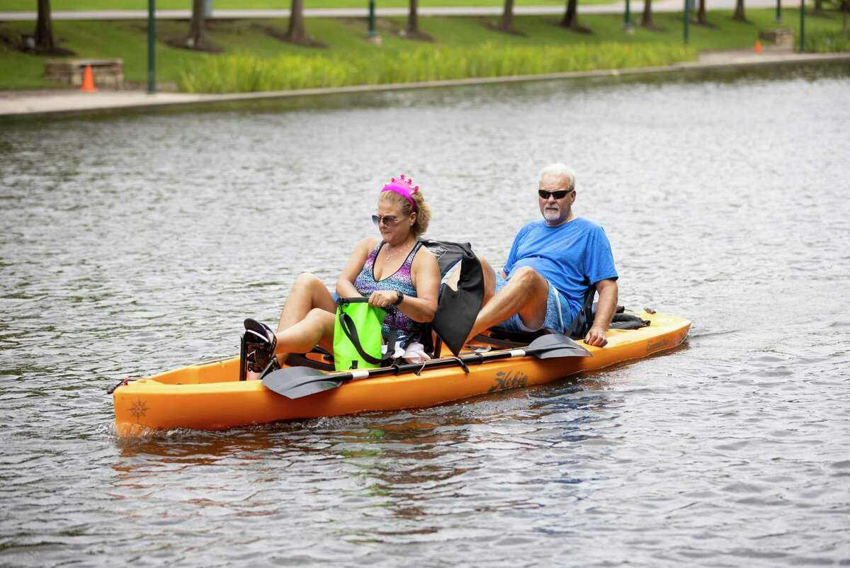 Two people peddle through the waterway in The Woodlands, Sunday, June 28, 2020. New equipment was added at the Riva Row Boat House for visitors to rent.