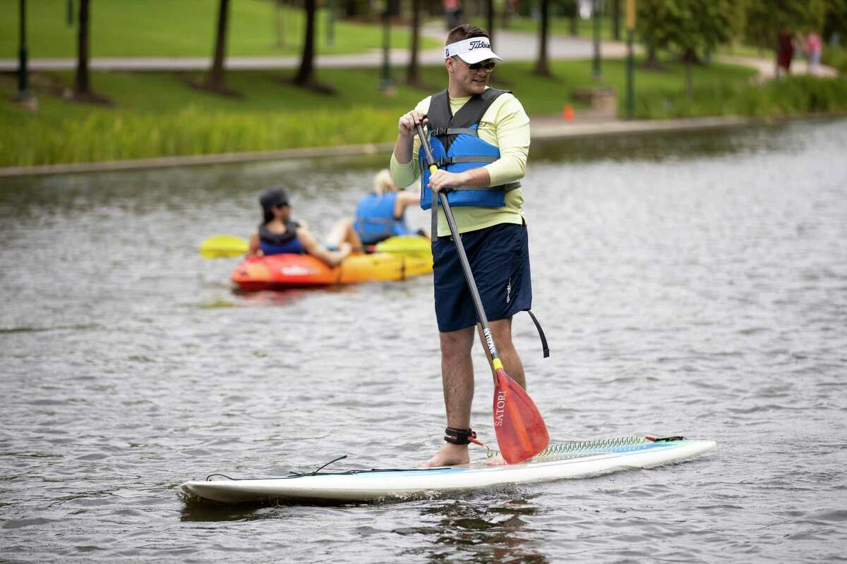 A man stands on a paddle board through the waterway in The Woodlands, Sunday, June 28, 2020. New equipment was added at the Riva Row Boat House for visitors to rent.