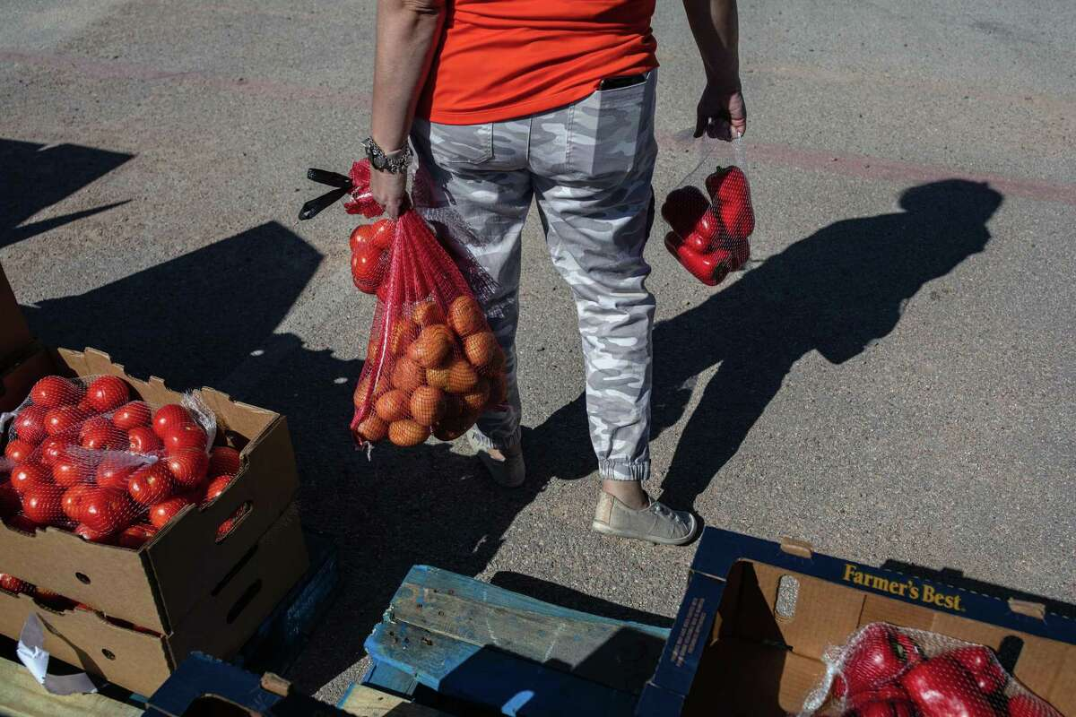 A staff member at the West Texas Food Bank in Odessa helps to distribute items at a drive-through pantry on April 24, 2020. Local business leaders say that as much as a third of the work force in the Midland-Odessa area could eventually lose their jobs. (Tamir Kalifa/The New York Times)