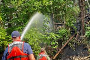 Firefighters put out a brush fire in Southbury, Conn., June 27, 2020.