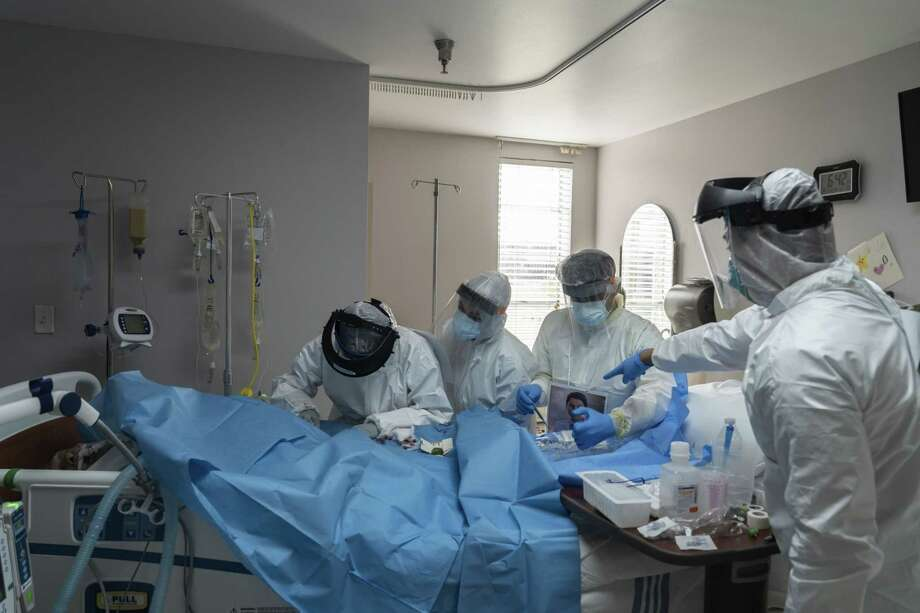 Medical workers wearing protective gear treat a patient in the covid-19 ICU at a hospital in Houston. Photo: Bloomberg Photo By Go Nakamura / Bloomberg