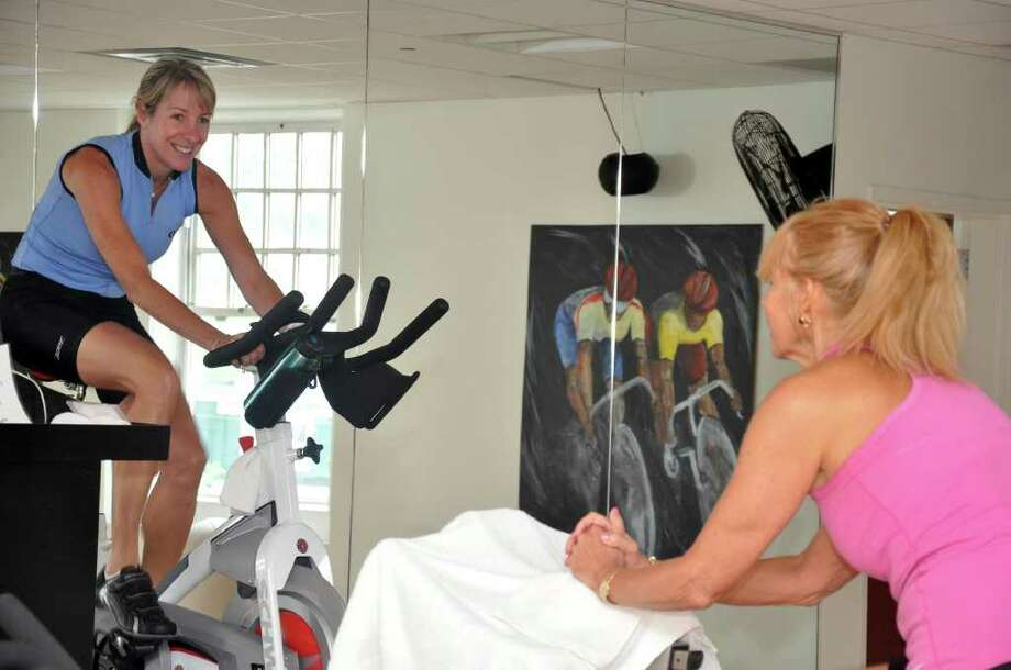 Darcy Ramsey, Fitness Director, motivates Betsy Heberling, of Greenwich, during a spinning class at the YMCA on Tuesday, Aug. 24, 2010. The Greenwich Family YMCA recently unveiled a newly revamped spin studio featureing 17 new, state of the art spin bikes. The bikes were purchased with the help of the generous support of members and friends of the YMCA, including a $12,000 contribution from ABILIS. Photo: Amy Mortensen / Connecticut Post Freelance