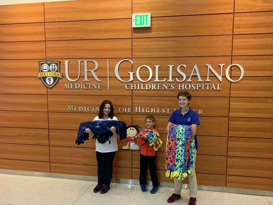 Tori Holmes, right, with sister Caitlin and brother Liam, delivers blankets she made to a Rochester, New York, children's hospital. The blankets are for families that are separated because of illness or another difficulty. Photo: Family Photo / Family photo