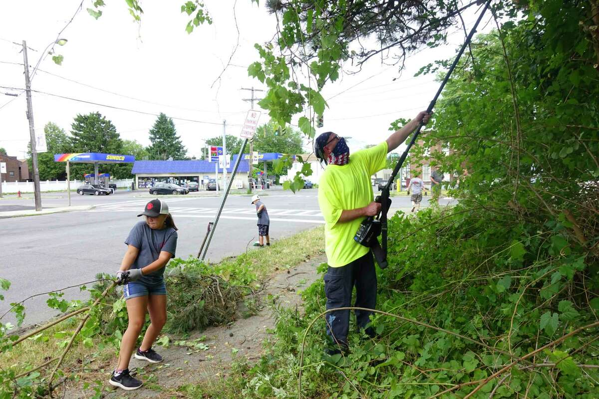 Volunteers, Bianca Scalise, 9, drags a tree limb as her uncle Tim Cavanaugh trims more branches off a tree in a small park on Tuesday, June 30, 2020, in Watervliet, N.Y. (Paul Buckowski/Times Union)