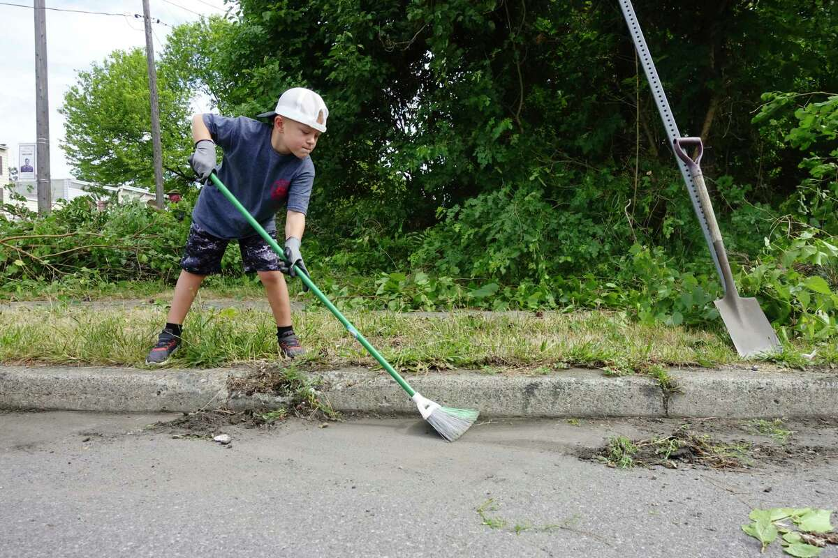Volunteer Anthony Scalise, 7, sweeps up weeds he removed from around the curb in a small park on Tuesday, June 30, 2020, in Watervliet, N.Y. (Paul Buckowski/Times Union)