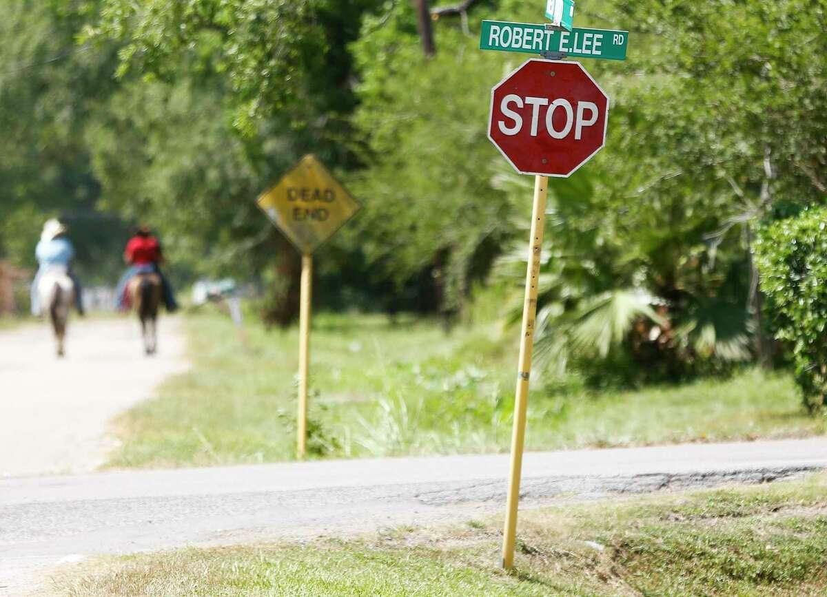 Horseback riders go down a street near Robert E. Lee Road in Houston on Thursday, June 18, 2020.