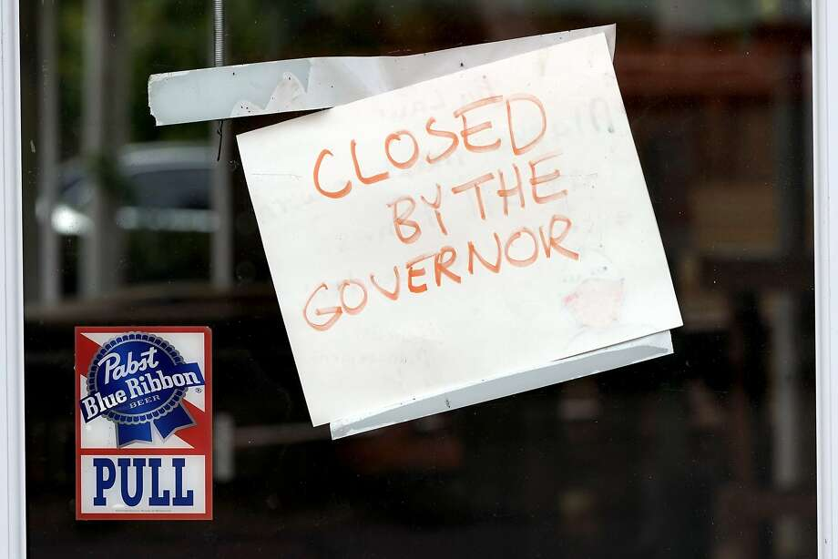 """A sign on the door of the West Alabama Icehouse reads """"Closed by the Governor"""", Monday, June 29, 2020, in Houston. Texas Gov. Greg Abbott shut down bars again and scaled back restaurant dining on Friday as cases climbed to record levels after the state embarked on one of America's fastest reopening. (AP Photo/David J. Phillip) Photo: David J. Phillip, Associated Press"""