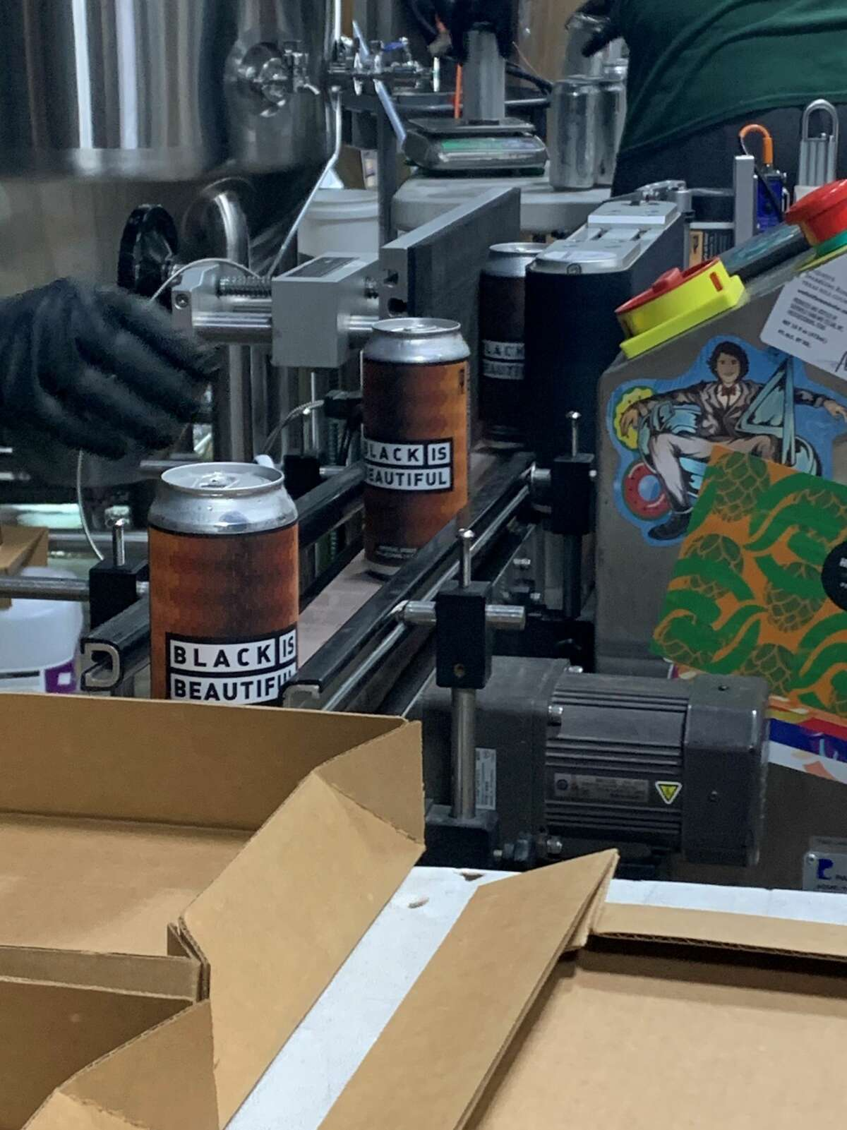 An employee of Weathered Souls Brewery places label on cans of its Black is Beautiful stout in San Antonio on Monday, June 29, 2020. The initiative behind the beer has grown from the local brewery's call for social justice into a worldwide campaign.