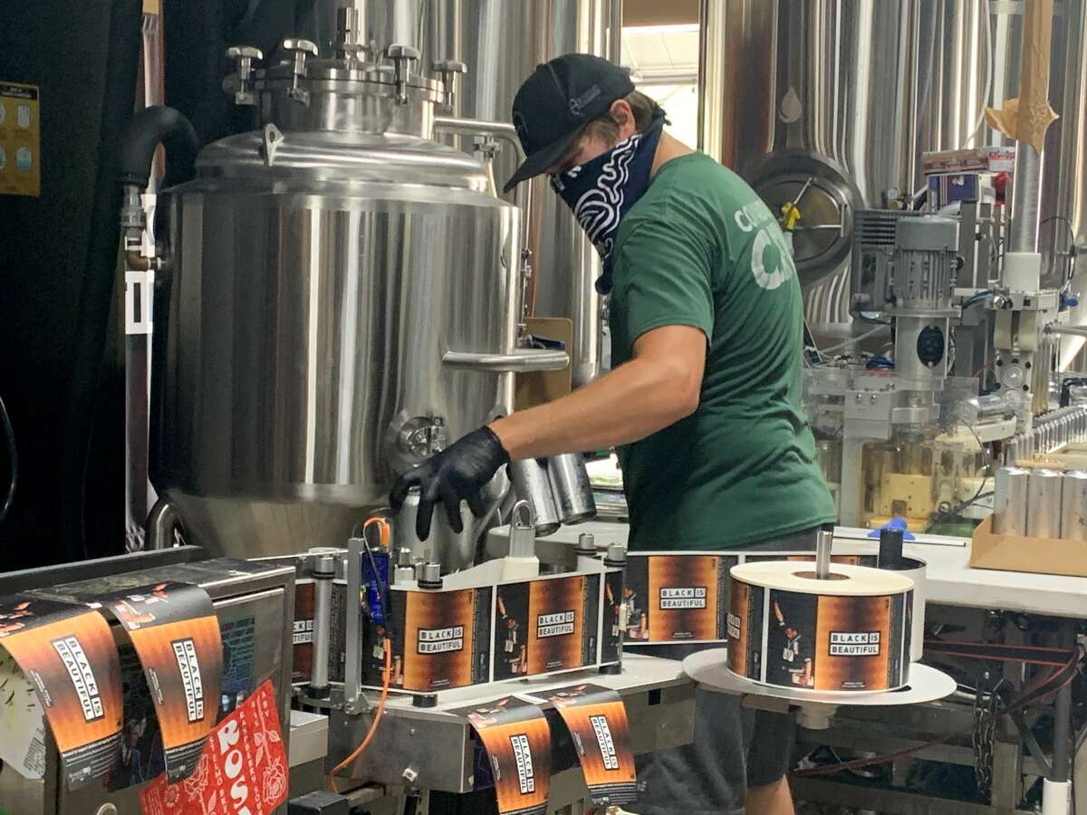 An employee loads silver cans of beer into a machine that will fit them with their Black is Beautiful labels at Weathered Souls Brewery on Monday, June 29, 2020, in San Antonio.The initiative behind the beer has grown from the local brewery's call for social justice into a worldwide campaign.