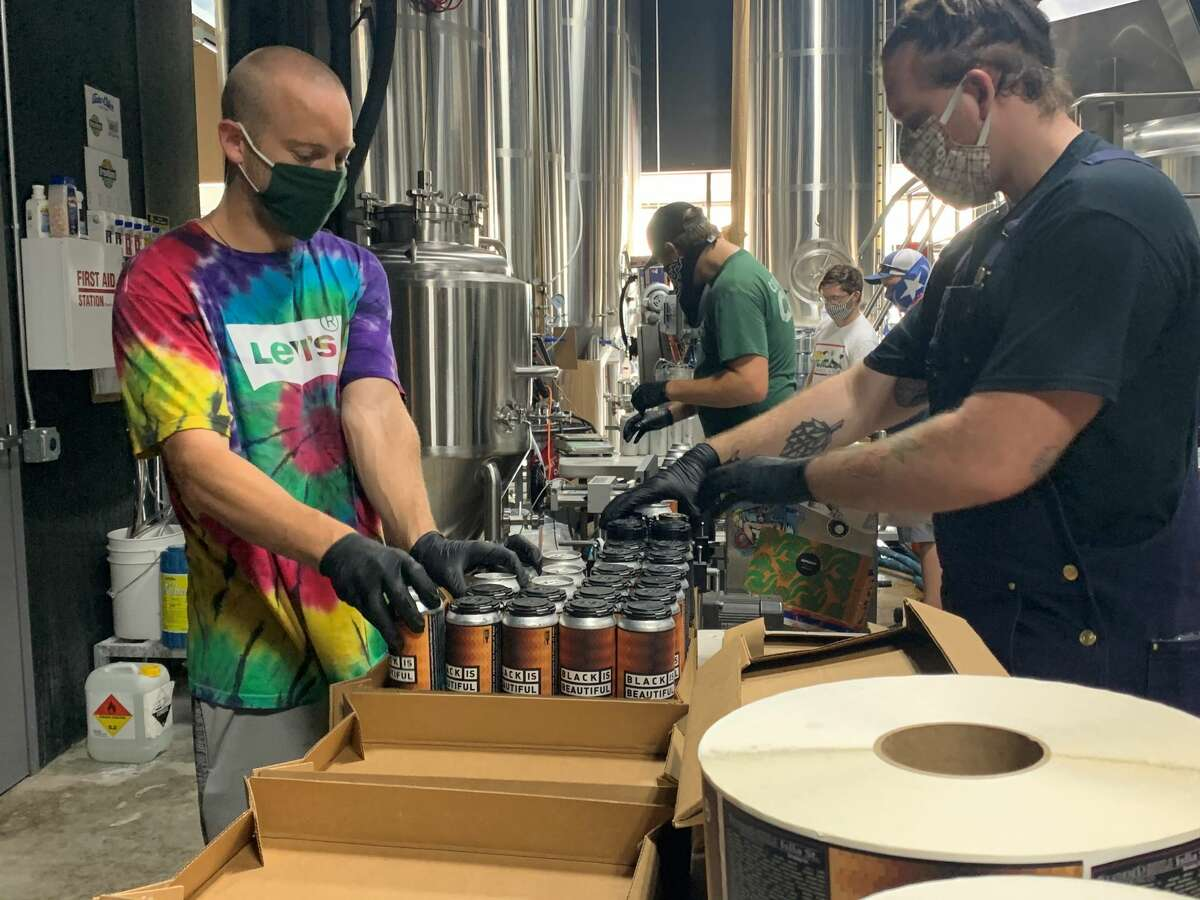 Employees of Weathered Souls Brewery package cases of its Black is Beautiful stout in San Antonio on Monday, June 29, 2020.The initiative behind the beer has grown from the local brewery's call for social justice into a worldwide campaign.