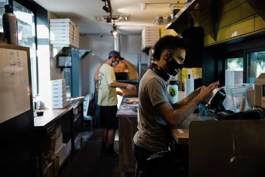 Nathan Coury, owner of Freak Brothers Pizza, right, and Josh Walker prepare to-go orders in their space at The Churchill in Phoenix on Friday, June 26, 2020. Photo: Photo For The Washington Post By Caitlin O'Hara / 2020 Caitlin O'Hara