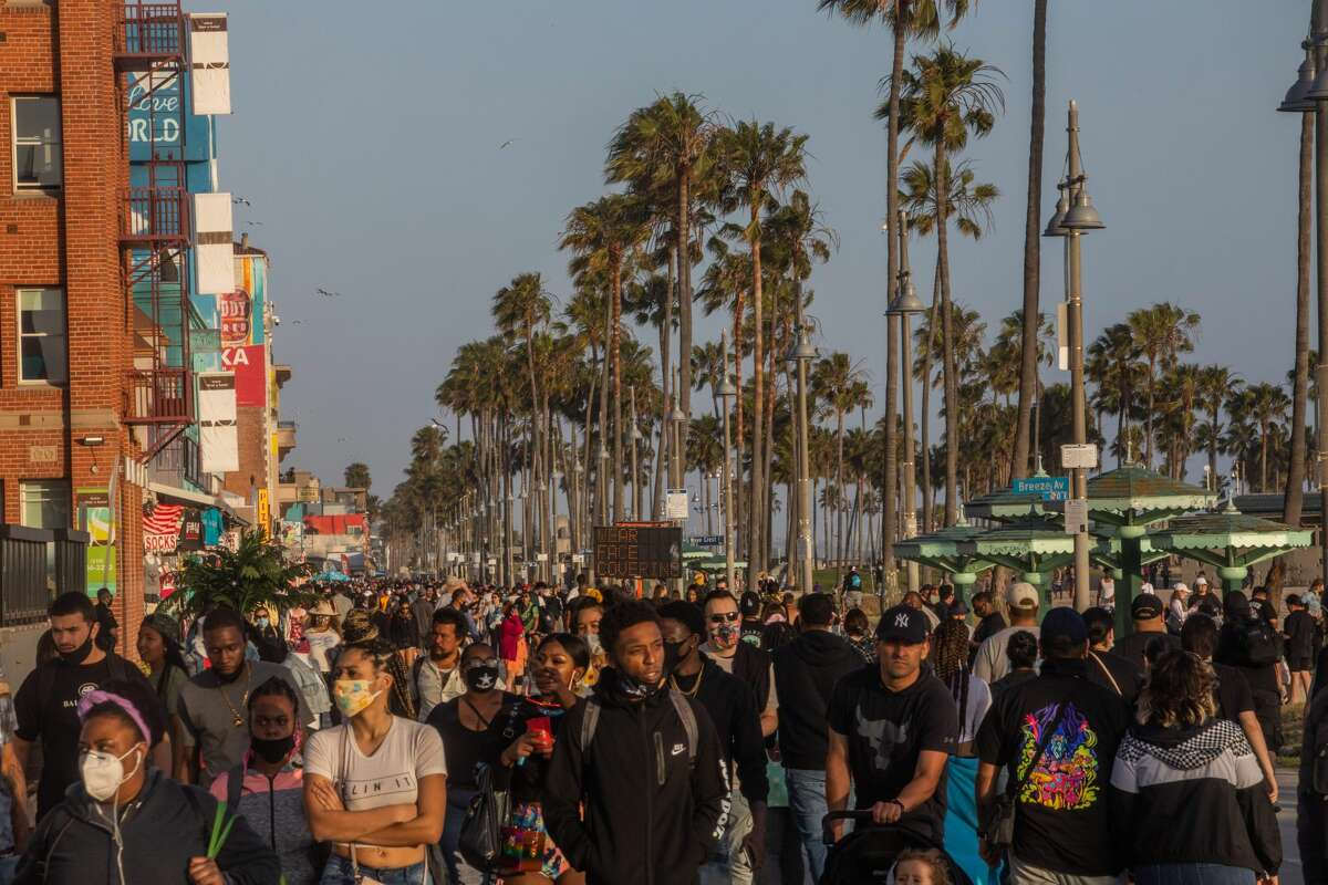 People walk at the boardwalk in Venice Beach during the first day of the Memorial Day holiday weekend amid the novel Coronavirus, COVID-19, pandemic in California on May 23, 2020. - Los Angeles County officials announced May 22, 2020, that beach bike paths and some beach parking lots will reopen and curbside service at indoor malls will be permitted. The county reopened its beaches a week ago but kept beach parking lots, bike paths, piers and boardwalks closed. (Photo by Apu GOMES / AFP) (Photo by APU GOMES/AFP via Getty Images)