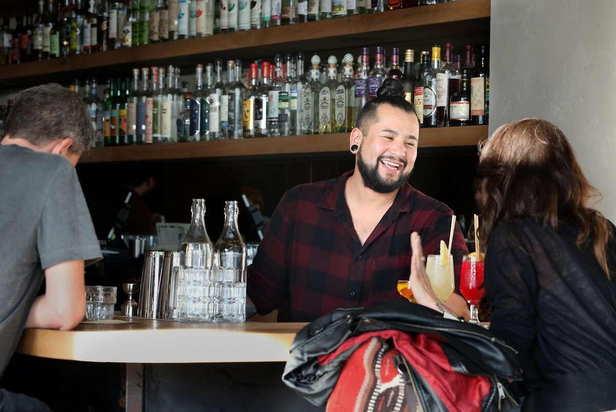 Bartender Christian Suzuki (middle) talks with Celisse Berumen (right) at Elda on Tuesday, Oct. 8, 2019, in San Francisco, Calif.