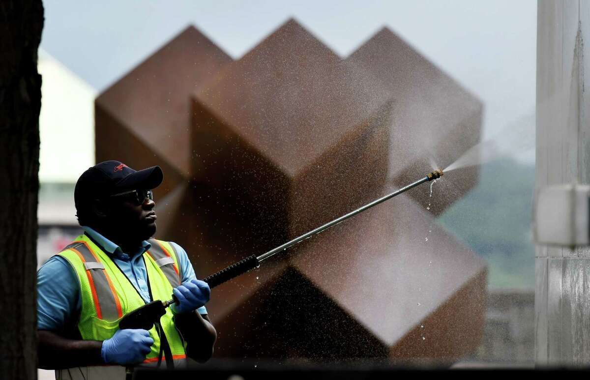 Empire State Plaza gets a thorough cleaning as a crew from the state Office of General Services power washes a marble wall near Antoni Milkowski's steel sculpture, titled