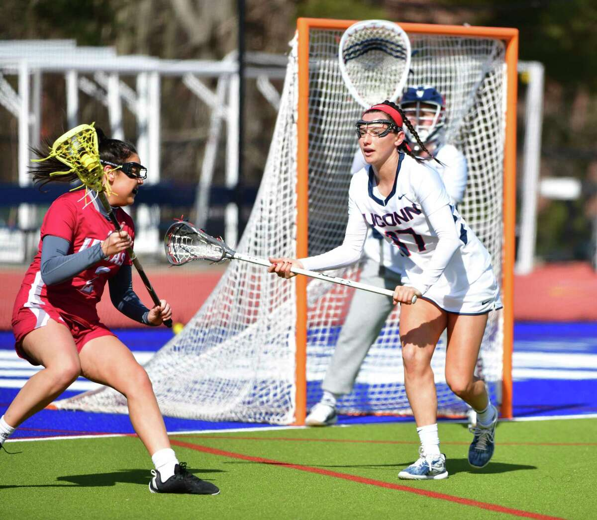 New Canaan's Julia Ozimek (17) of the University of Connecticut women's lacrosse team defends against a University of Massachusetts attacker during a game on March 7, 2020.