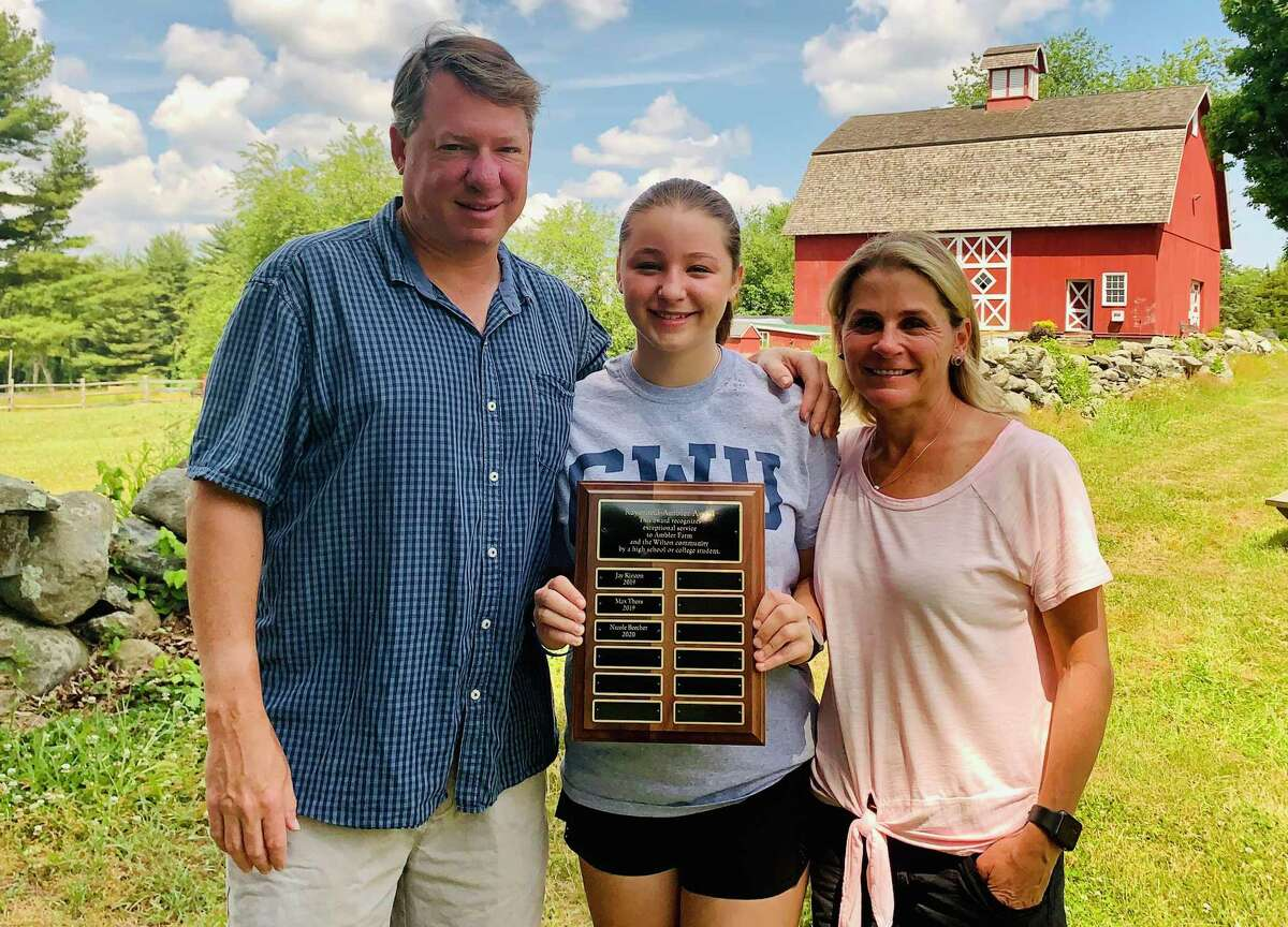 Nicole Beecher, shown with her parents James and Sharon Beecher, holds the plaque recognizing her as the recipient of Ambler Farm's 2020 Raymond-Ambler Award.