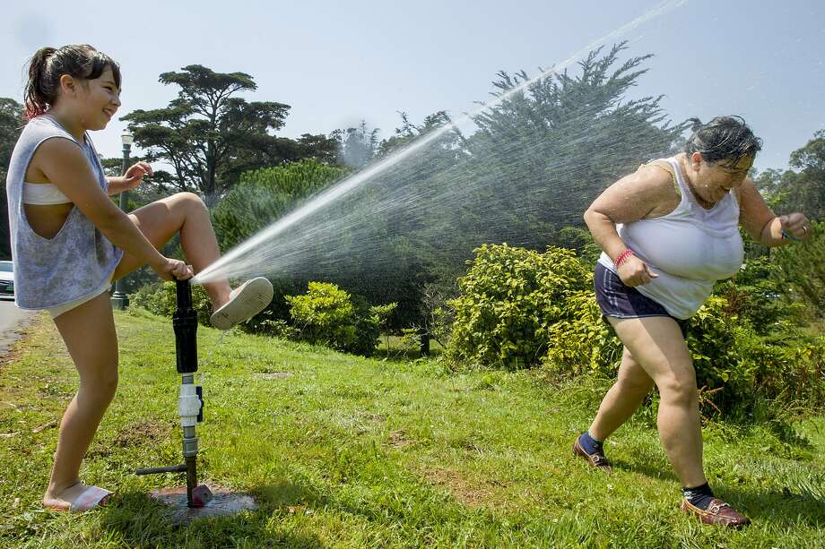 Amilia Madigan, 11, and mother Desy Stoyanov cool off during a September 2017 heat wave using the sprinklers at Golden Gate Park in San Francisco. Photo: Santiago Mejia / The Chronicle 2017