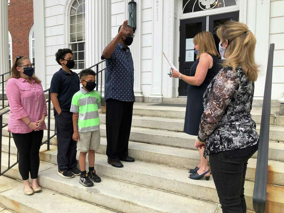 Stratford Town Clerk Susan Pawluk swears in Lorenzo Elder as a member of the Stratford Board of Zoning Appeals June 30, 2020 as Elder's wife, Jessica, sons Carter and Chance, and Mayor Laura Hoydick look on. Photo: Ethan Fry / Hearst Connecticut Media
