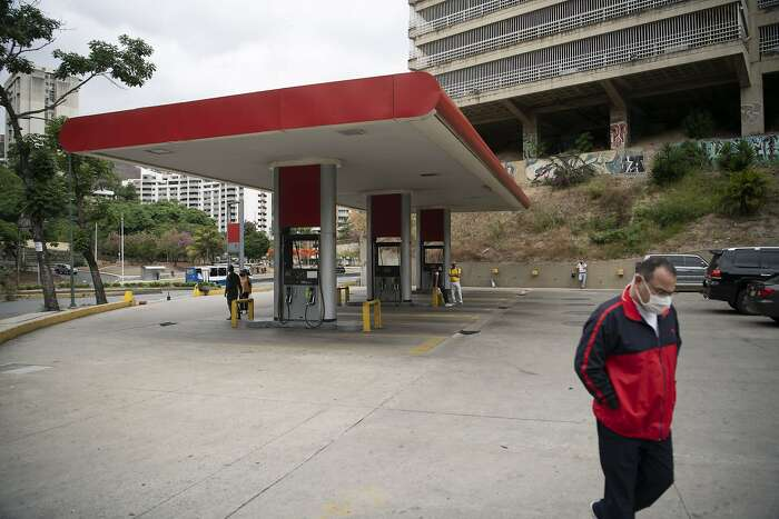 A pedestrian wearing a protective mask walks past an empty Petroleos de Venezuela SA (PDVSA) gas station in Caracas, Venezuela, on Monday, June 1, 2020. Venezuela's President Nicolas Maduro said fuel prices would increase starting in June, a historic policy shift after decades of subsidies that have allowed Venezuelans to essentially fill their tanks for free. Photographer: Carlos Becerra/Bloomberg