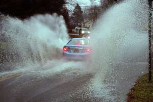 Cars travel through a flooded Broadbridge Road in Bridgeport, Conn., on Friday, Dec. 28, 2018.