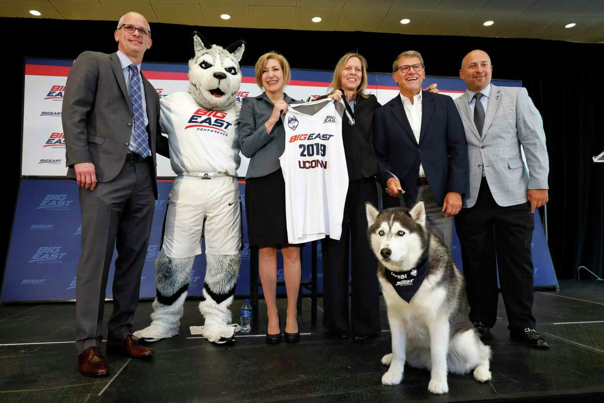UConn men's basketball coach Dan Hurley, left, University President Susan Herbst, third left, Big East Commissioner Val Ackerman, fourth left, women's basketball coach Geno Auriemma, fifth left, and Director of Athletics David Benedict, pose for photos in 2019 during the announcement that UConn is re-joining the Big East Conference.