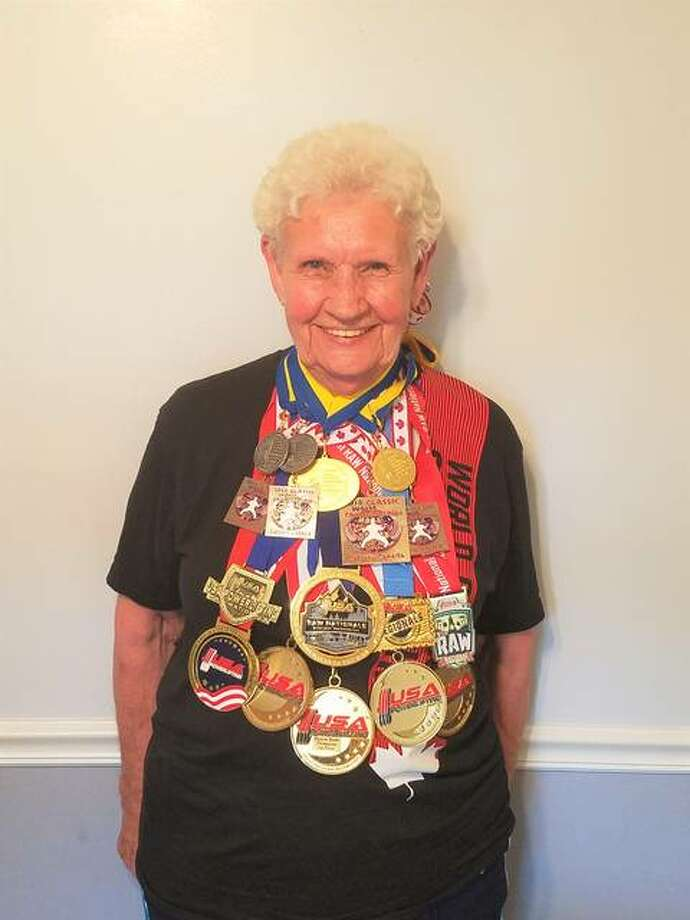 "Rosewood Heights resident Shirley Webb, 82, wearing 17 of her 18 medals. The ""weightlifting grandma,"" as described in the book ""Ripley's Believe It or Not! Shatter Your Senses!,"" since Dec. 9, 2016, when her son, Kent Webb, started recording and tracking the total amount of weights lifted, has lifted more than four million pounds, as of this past May. Photo: For The Telegraph"