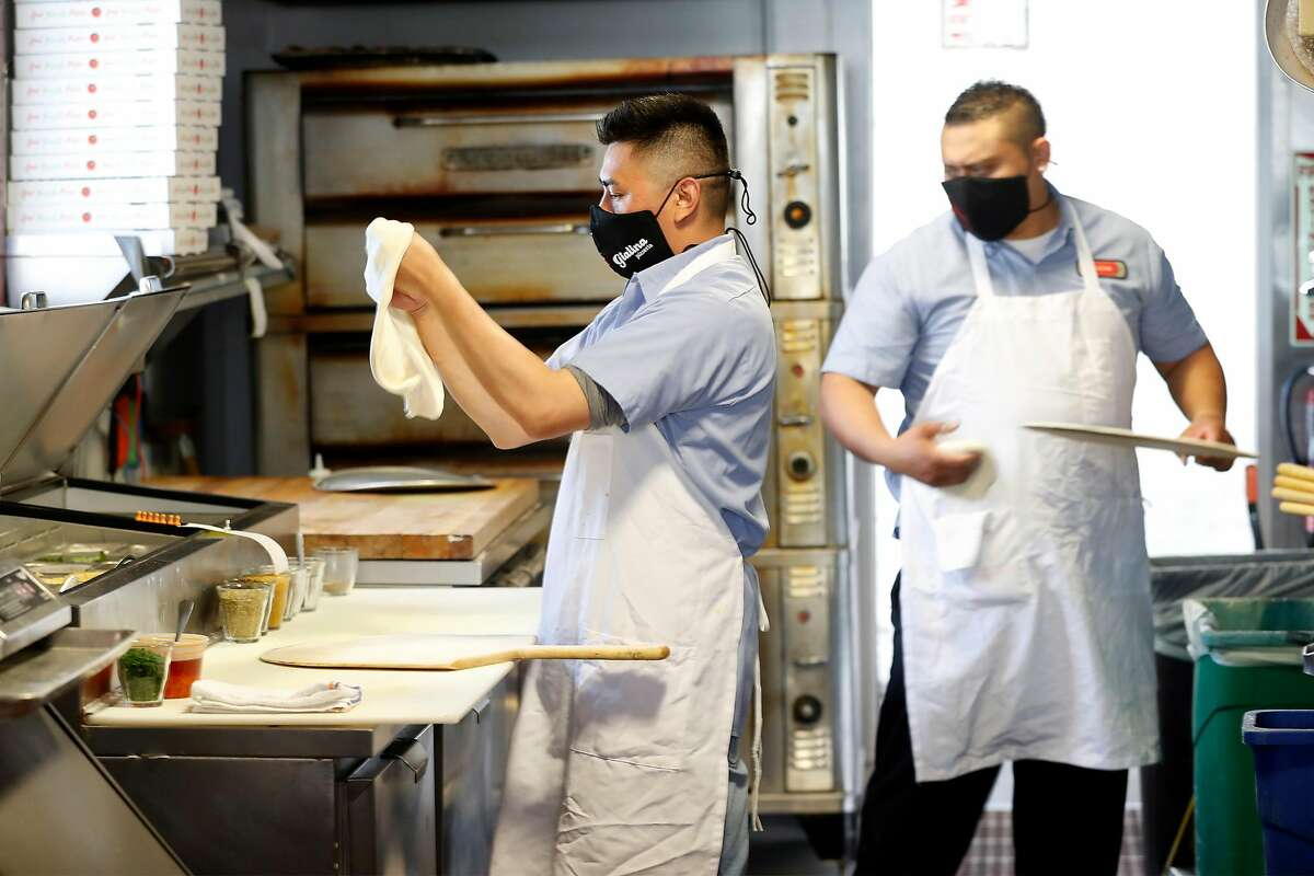 Luis Quintero and Irvin Tamaal work in the kitchen at Gialina Pizzeria in San Francisco, Calif., on Monday, June 29, 2020. On July 1st, the California state minimum wage will increase to $12.00 for employers with 25 employees or less, and $13.00 for employers with 26 employees or more.