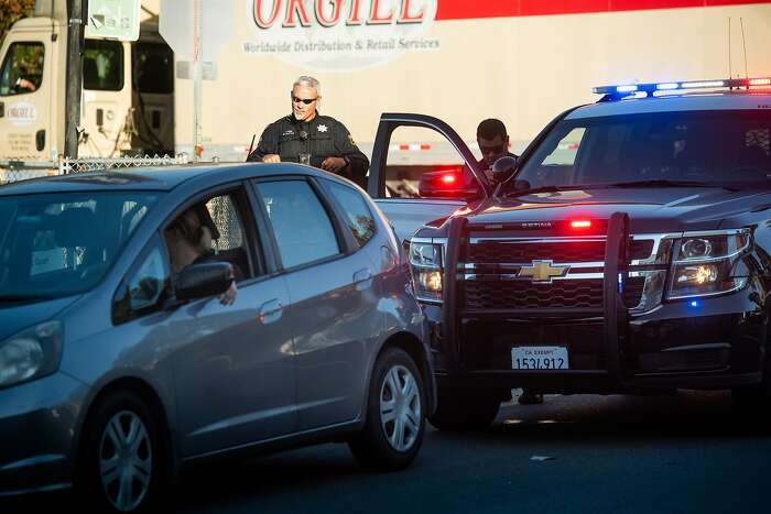 Berkeley Police Officer Mathis keeps an eye on a vehicle while Officer Garrison, right, issues a citation during a crackdown on railroad crossing violations in Berkeley, Calif., on Tuesday, Sept. 24, 2019. Officer Mathis said the driver was cited for cell phone use while crossing the tracks.