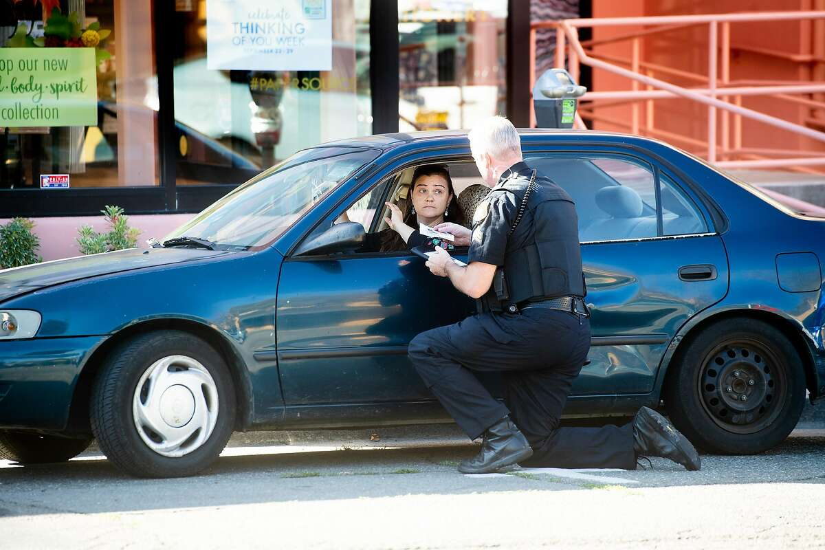 A driver, who declined to be identified, receives a warning from Berkeley police Sgt. Rittenhouse during a crackdown on railroad crossing violations in Berkeley, Calif., on Tuesday, Sept. 24, 2019. Sgt. Rittenhouse said the motorist drove around a closed railroad crossing gate as a train approached.