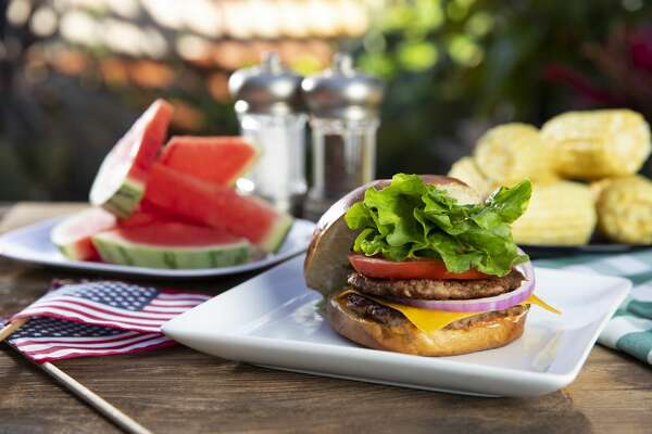 This is a close-up photographs of an open faced cheeseburger on a white plate surrounded by watermelon and corn on the cob sitting on a wooden table in an outdoor setting. This photograph would work well for the Fourth of July holiday or labor day and memorial day.