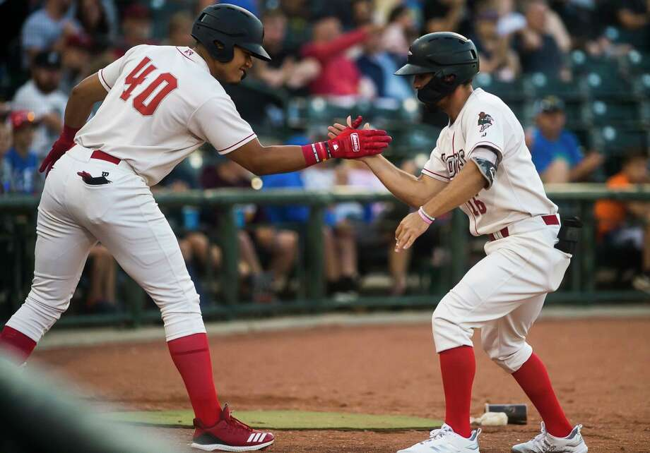 Great Lakes Loons' Luke Heyer (right) high-fives teammate Romer Cuadrado after Heyer hit a three-run homer vs. the Lake County Captains in 2019. Photo: Daily News File Photo