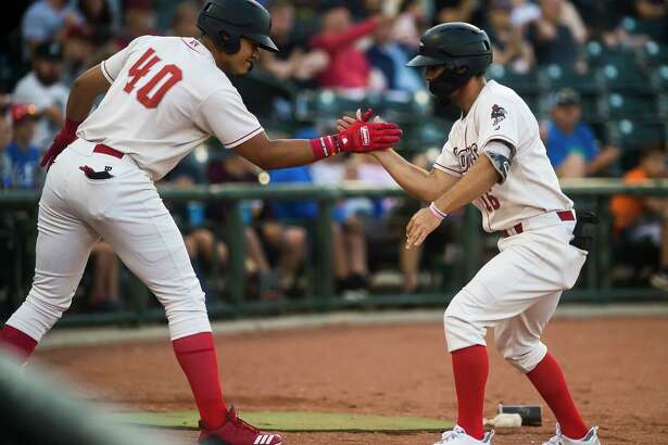 Great Lakes Loons' Luke Heyer (right) high-fives teammate Romer Cuadrado after Heyer hit a three-run homer vs. the Lake County Captains last August.
