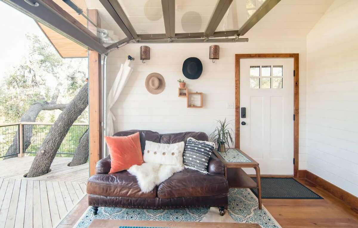 There's plenty of natural light inside this living space. You'll find a leather loveseat, a coffee table on a cowhide rug, all under the big glass-paneled overhead door that slides up to allow direct access to the large deck.