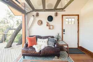 There's plenty of natural light inside this living space. You'll find a leather love seat, a coffee table on a cowhide rug, all under the big glass-paneled overhead door that slides up to allow direct access to the large deck.