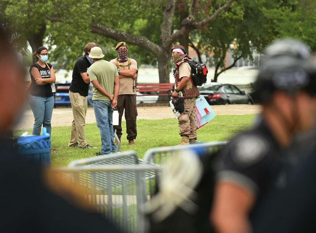 """<p>Demonstrators watch as San Antonio police stand guard around the Christopher Columbus statue after a demonstration in the park Saturday afternoon.</p>""""></li></ul>    <p style="""