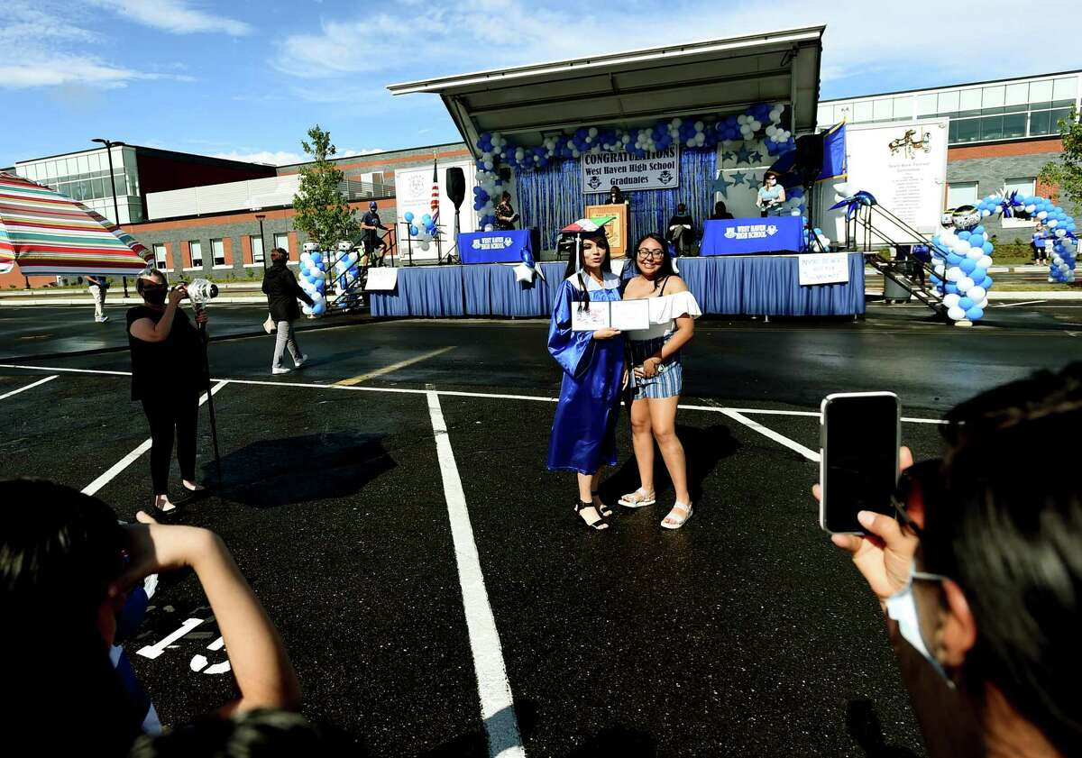 West Haven, Connecticut - Tuesday, June 30, 2020: West Haven High School holds a speedy drive-in graduation ceremony Tuesday evening as seniors arrive in waves of 35 cars at a time,walk up to the stage and receive their diplomas, and have their photographs made in cap & gowns. Approximately 381 seniors graduated from the high school.