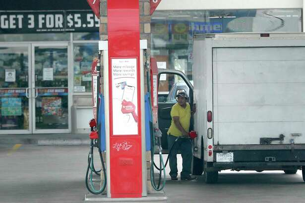A man pumps gas at a Heights area gas station, Tuesday, June 30, 2020, in Houston . Story on Fourth of July travel and gas demand outlook.